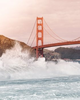 Crashing waves by a red bridge in San Francisco