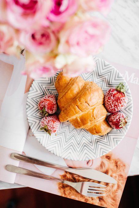 Croissant on a plate near with strawberies