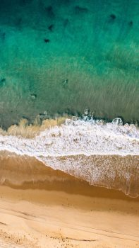 Drone view of ocean waves and sand coast
