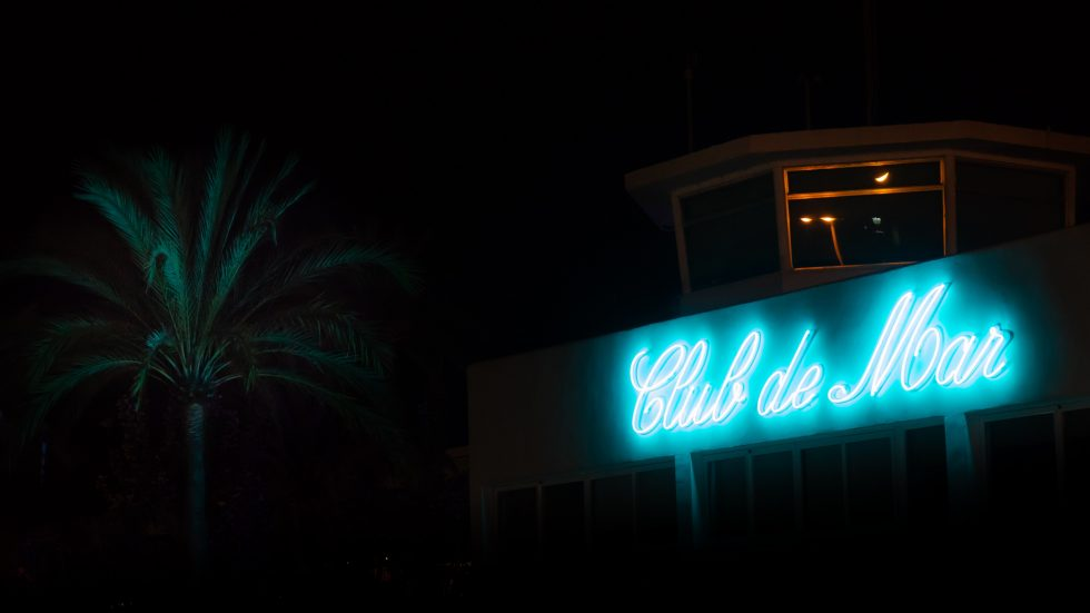 A blue neon sign of Club De Mar near a palm tree