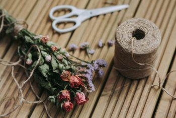 A dried flowers bouquet beside a twine coil and white scissors