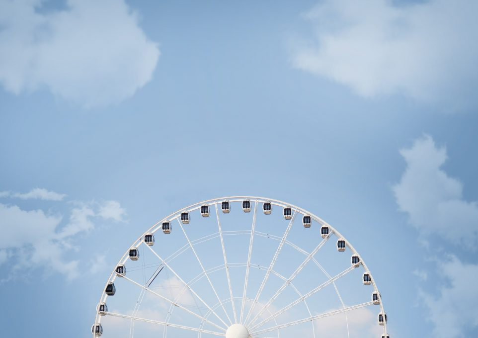 A half of a white Ferris wheel against the blue sky