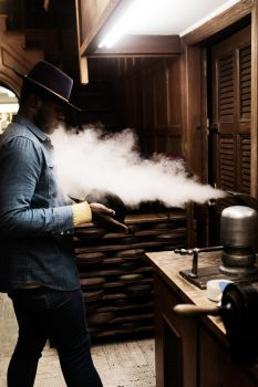 A hat maker wearing a hat standing with steam blowing out