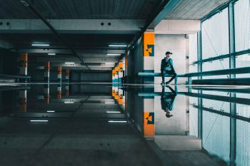 A man reflected in the water on the floor in an empty building