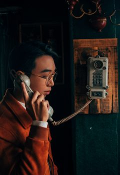 A man wearing a red jacket and glasses holding a gray cradle telephone