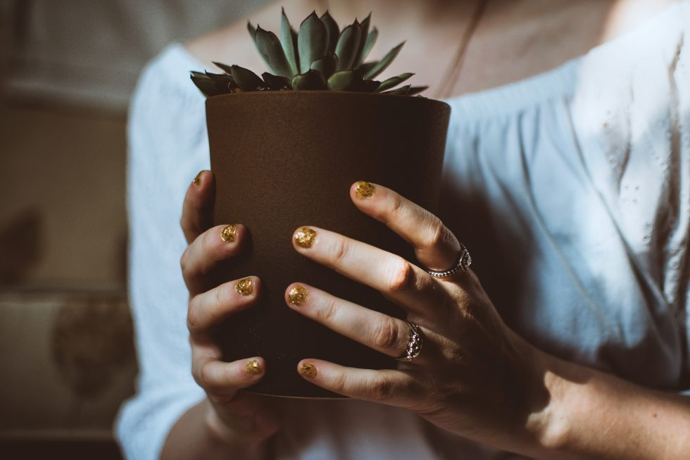 A person holding a brown plant pot