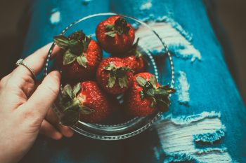 A person holding a clear glass bowl of strawberries