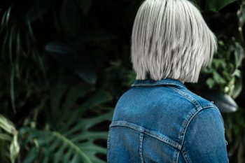 a-person-wearing-a-blue-denim-jacket-on-the-background-of-lush-greenery