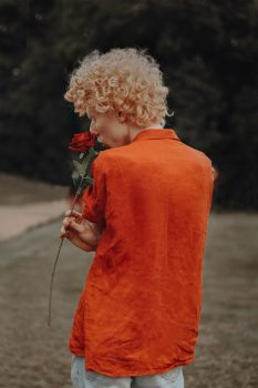 A person wearing orange dress shirt holding a red rose