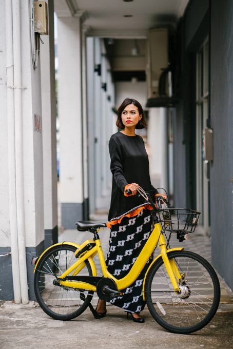 A woman holding a yellow bike at daytime