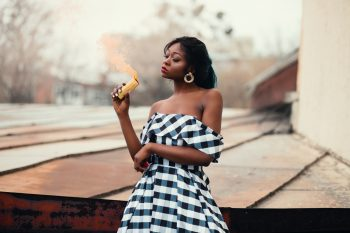 A woman in a black and white off-shoulder dress holding a smoke bomb
