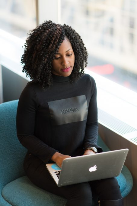 A woman in a black long-sleeved shirt using MacBook