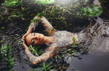 A woman in a long-sleeved dress surrounded by water plants