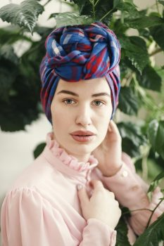 A woman in a pink long-sleeved top and blue and red headdress