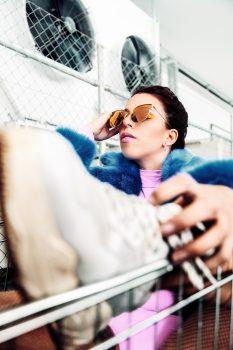 A woman sitting in a shopping cart and holding brown sunglasses