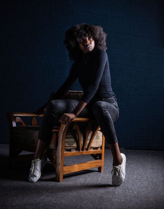 A woman sitting on an arm of an armchair against a black wall