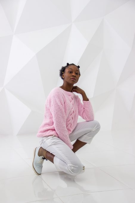 A woman wearing a pink sweater and white pants posing