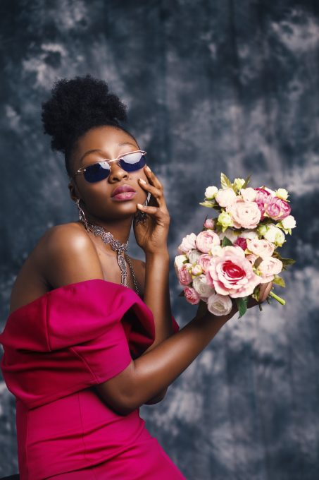 A woman wearing sunglasses and posing with a flowers bouquet