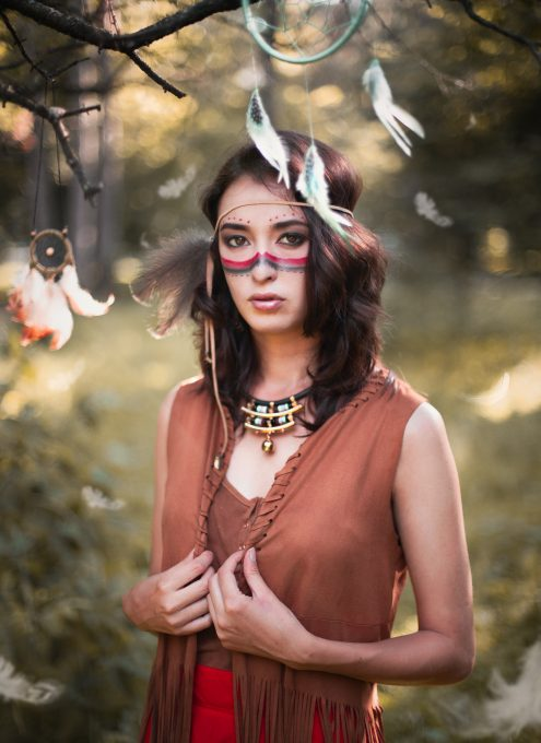 A woman with Native American face painting and dream catchers in nature