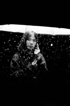 Black and white photography of a woman holding an umbrella