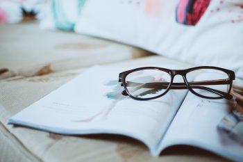 Black framed eyeglasses on an open magazine