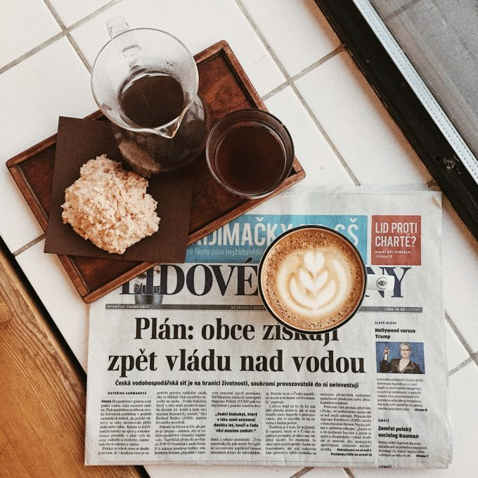 Breakfast with a cup of cappuccino standing on a newspaper