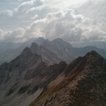 Brown and gray mountains under a cloudy sky