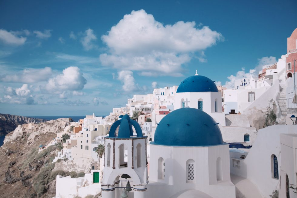 Church in Santorini, Greece overlooking houses, cliffs, and the sea