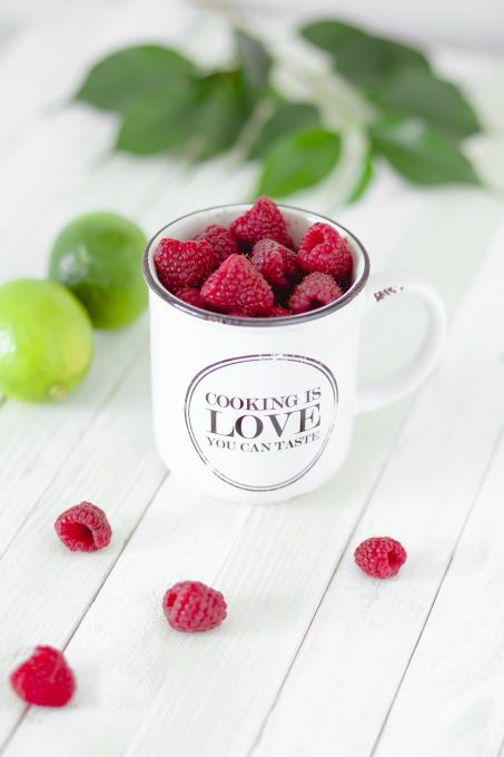 Close-up photo of an enamel cup filled with raspberries