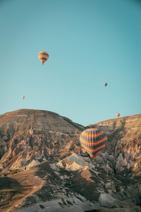Hot air balloons floating above mountains