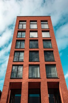 Low angle photo of a red and black concrete high-rise building