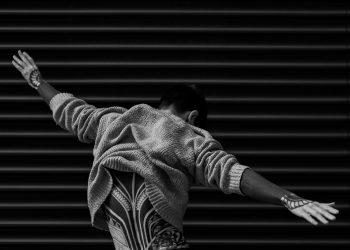 Monochrome photo of a man raising his hands