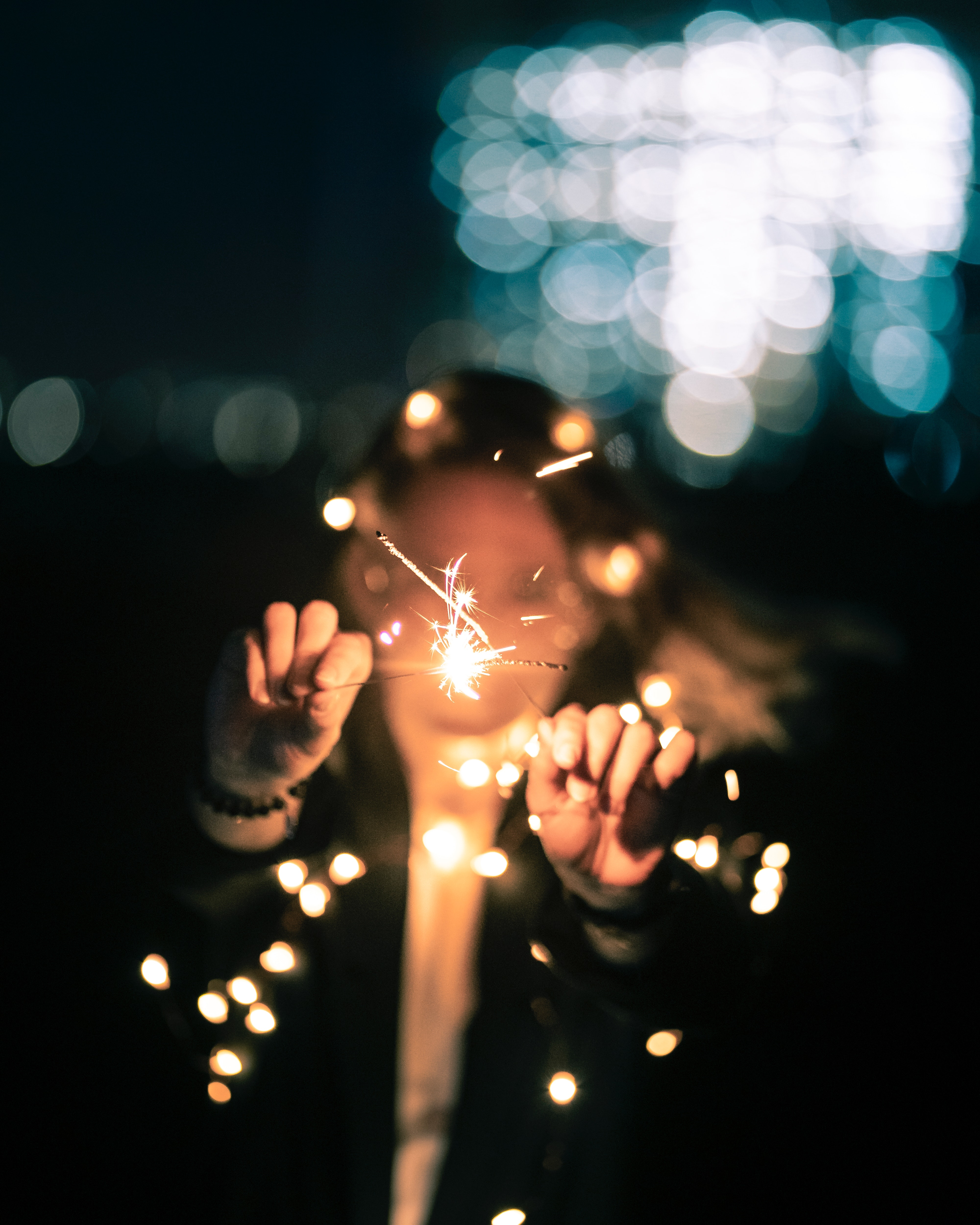 Selective focus photo of a woman holding sparklers