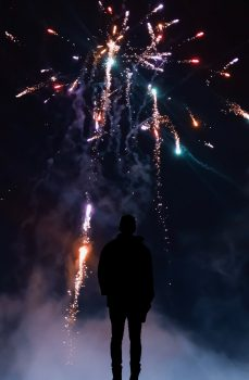 Silhouette of a person in front of fireworks