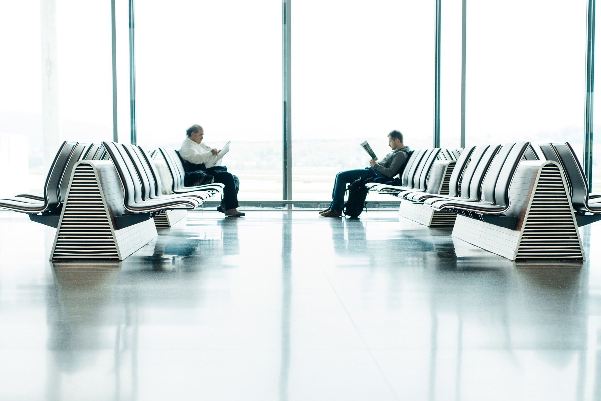 Two men sitting in front of each other in the airport waiting area