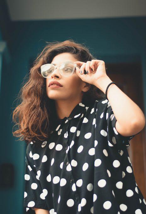 Woman wearing polka-dot shirt holding eyeglasses