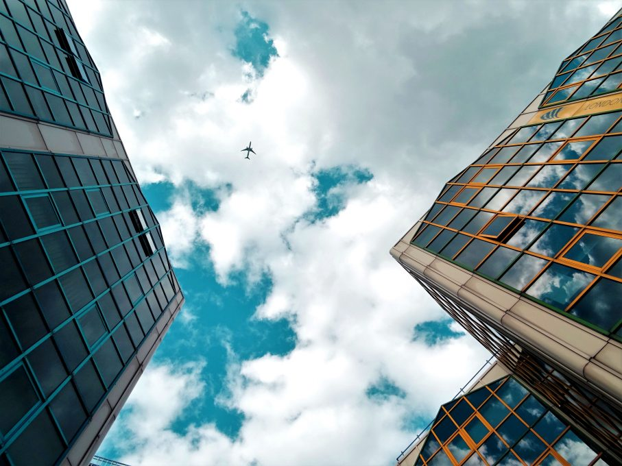 Worm's eye view of buildings and a plane flying between them