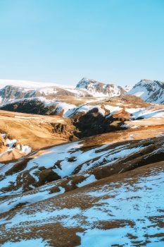 A brown mountain with snow during the daytime