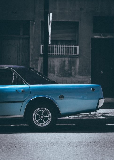 A classic blue sedan parked on the roadside