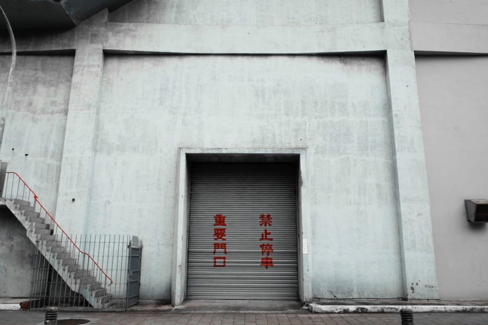 A facade of a gray building with a gate closed by roller shutter
