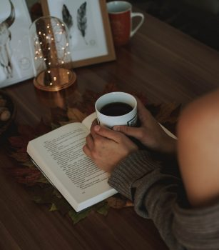 A girl holding a mug of coffee above an opened book on a wooden table