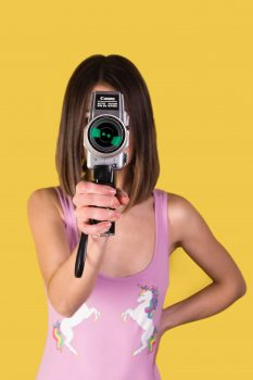 A girl wearing a pink tank top holding Canon camera