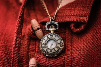 A gold-colored chain necklace with watch pendant