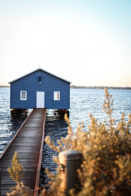 A house with a dock on the body of water under a blue and white sky