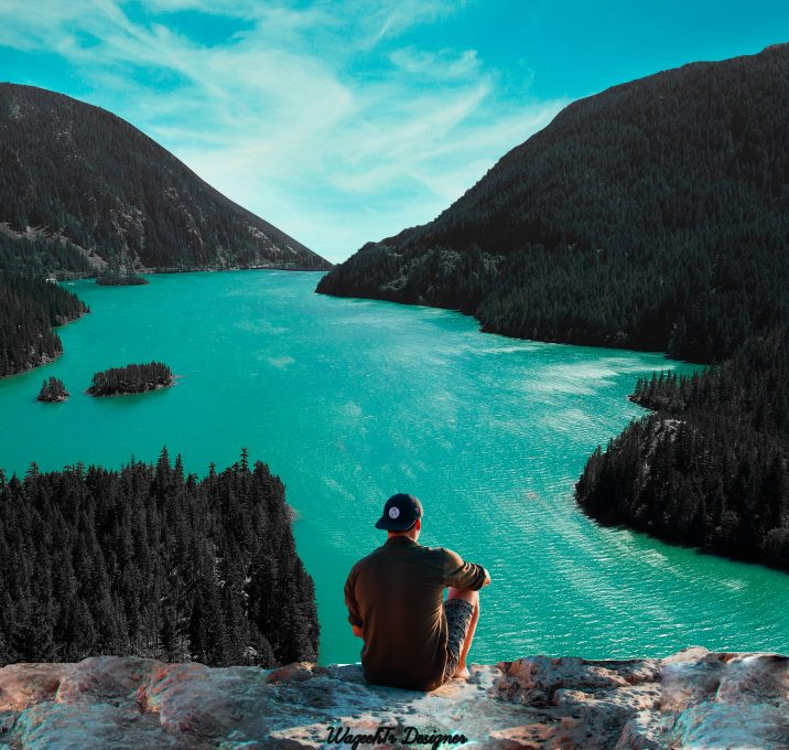 A man sitting on a cliff in front of the body of water