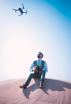 A man sitting on a desert ground looking up and operating a quadcopter