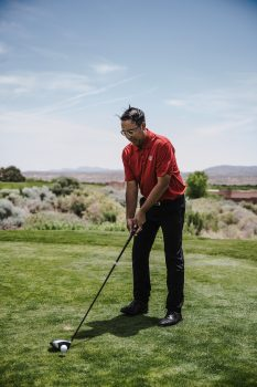 A man wearing a red t-shirt playing golf