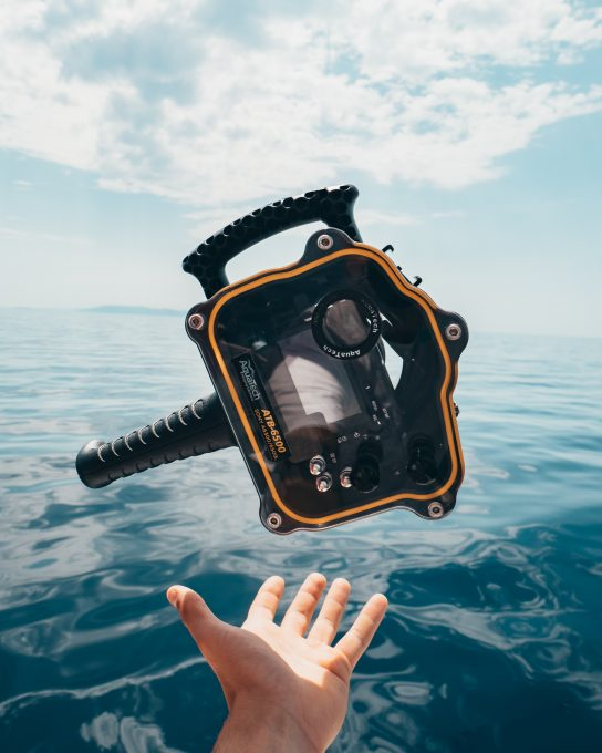 A person grabbing black and orange plastic case in front of calm water