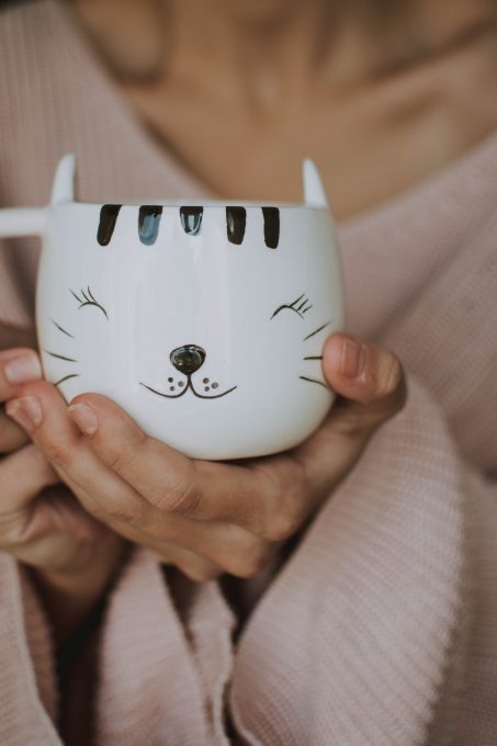 A person holding a white cat mug