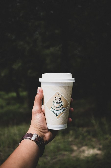 A person holding a white disposable cup on the background of a forest